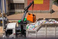 Un camion à ordures soulève les réservoirs avec une grue et les verse dans le corps images libres de droits