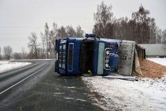 Un camion con segatura si è girato nella carreggiata sdrucciolevole fotografia stock libera da diritti