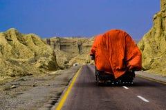 Un camion conduisant sur la route avec le ciel bleu et les montagnes ! Photographie stock