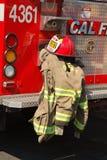 Un camion dei vigili del fuoco e rivestimento di caloria con il cappello fotografia stock