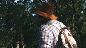 Un campesino joven que camina en el bosque Caminante que camina en bosque en la puesta del sol Forma de vida activa Llevar una ca metrajes