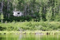 Un campeur caché dans les arbres près de l'eau photo stock