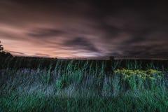 Un campo che entra nella notte fotografia stock