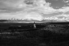 Un campo con una iglesia en la distancia con el cielo nublado hermoso fotos de archivo