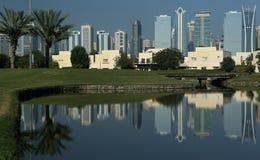 Un campo de golf en Dubai con las palmeras y los rascacielos en el fondo imagen de archivo libre de regalías