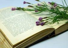 Un campo florece en un libro abierto Todavía vida con un libro abierto de Honore de Balzac Fotos de archivo