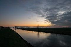 Un canal holandés se cubre con hielo Un molino de viento distante se siluetea contra el cielo de igualación imagen de archivo