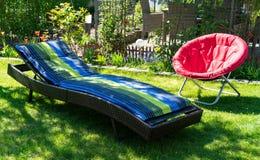 Un canapé bleu et vert du soleil et une chaise se pliante rouge de lune dans un jardin au soleil photos libres de droits