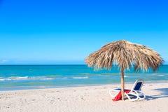 Un canapé du soleil sous un parapluie sur la plage sablonneuse par la mer et le ciel Fond de vacances Horizontal idyllique de pla photographie stock