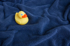 Un canard en caoutchouc jaune sur la serviette onduleuse bleue Photo libre de droits