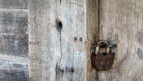 Un candado del hierro en la puerta de madera de una choza del pueblo Material natural Foto de archivo libre de regalías