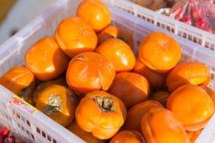 Un canestro in pieno dei cachi arancio Fotografie Stock