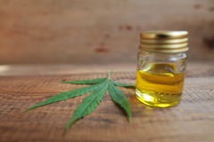 Un cannabis pousse des feuilles et une bouteille de table en bois d'huile de chanvre photographie stock