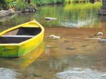 Un canoë jaune dans le lac, l'eau claire Photo stock