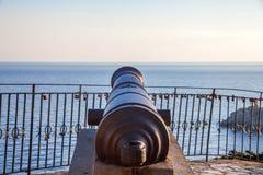 Un canon se dirigeant vers la mer L'artillerie antique se reposant au-dessus du bloc de béton Une mer calme entoure la statue Rev photographie stock