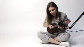 Un cantante con un pequeño ukelele de la guitarra metrajes