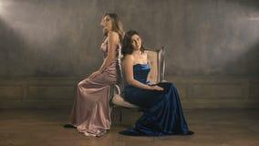 Un cantante di due ragazze si siede su una sedia e canta longshot 4k Vestiti lussuosi da sera blu e rosa Donna bionda e castana archivi video