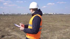 Un capataz un constructor marca datos sobre un campo vacío para comenzar a construir un nuevo edificio, un área residencial, indu almacen de metraje de vídeo