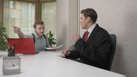 Un capo arrabbiato grida al suo giovane subalterno, impiegato Lavoro nell'ufficio Fps di concetto 60 di conflitto video d archivio