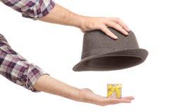 Un cappello con una scatola di regalo di mano del ` s dell'uomo fotografia stock