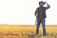 Un cappello da cowboy dell'uomo e un loso nel campo Agricoltore americano in una f Fotografie Stock Libere da Diritti
