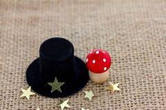 Un cappello del cilindro, un fungo della mosca e le stelle si trovano su tessuto Fotografia Stock Libera da Diritti