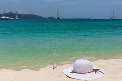 Un cappello femminile bianco si trova sulla sabbia sulla spiaggia Bella vista della vista sul mare con le navi sull'orizzonte Fotografie Stock Libere da Diritti