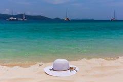 Un cappello femminile bianco si trova sulla sabbia sulla spiaggia Bella vista della vista sul mare con le navi sull'orizzonte Fotografia Stock