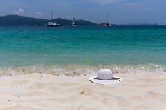Un cappello femminile bianco si trova sulla sabbia sulla spiaggia Bella vista della vista sul mare con le navi sull'orizzonte Fotografie Stock