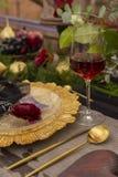 Un capullo de rosa rojo, mintiendo en un disco de oro, al lado de un vidrio de rojo Foto de archivo libre de regalías