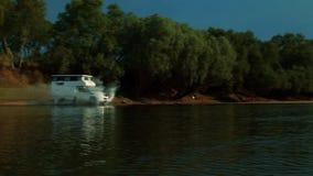 Un caravan che accelera attraverso la superficie di un fiume archivi video