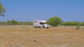 Un caravan che guida attraverso il bushland asciutto archivi video