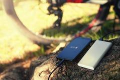 Un cargador portátil carga el smartphone Accione el banco con el cable contra la perspectiva de la madera y de la bicicleta fotografía de archivo