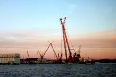 Un cargo cranes en el puerto en la puesta del sol Fotografía de archivo