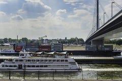 Un cargo et un bateau de passanger passant sous le pont d'Oberkasseler dans Duseldorf, Allemagne un jour nuageux photo stock