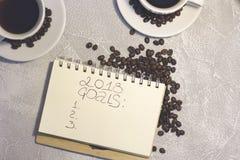 Un carnet avec l'inscription de 2018 buts avec deux tasses de café Image stock