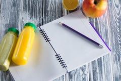 Un carnet avec un crayon et des bouteilles de plan rapproché de jus sur une table légère en bois L'espace libre pour une inscript Images libres de droits