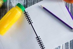 Un carnet avec un crayon et des bouteilles de plan rapproché de jus sur une table légère en bois L'espace libre pour une inscript Photos stock