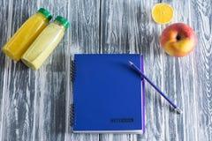 Un carnet avec un crayon, une pomme, des jus et une moitié d'un citron sur une table légère en bois L'espace libre pour l'inscrip Image stock