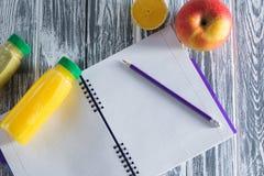 Un carnet avec un crayon, une pomme, des jus et une moitié d'un citron sur une table légère en bois L'espace libre pour une inscr Image libre de droits
