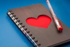 Un carnet avec un grand coeur rouge sur un fond bleu, Photos libres de droits