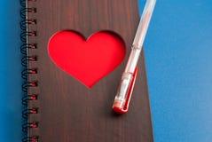 Un carnet avec un grand coeur rouge sur un fond bleu, Photographie stock