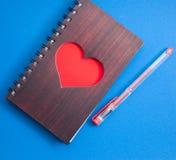 Un carnet avec un grand coeur rouge sur un fond bleu, Photo libre de droits