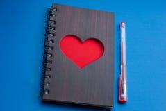 Un carnet avec un grand coeur rouge sur un fond bleu, Image stock