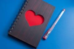 Un carnet avec un grand coeur rouge sur un fond bleu, Images libres de droits