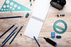 Un carnet blanc sur un fond en bois au-dessus duquel un stylo bille a accroché Il y a de papeterie sur la table Copyspace photographie stock
