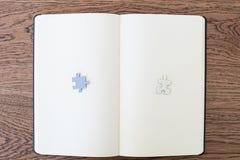 Un carnet blanc sur une table en bois avec deux morceaux de puzzle, un W photographie stock libre de droits
