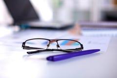 Un carnet, ordinateur portable, stylo, document sur papier de graphique sur la table de bureau derrière les abat-jour blancs Photo libre de droits