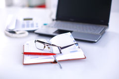 Un carnet, ordinateur portable, stylo, document sur papier de graphique sur la table de bureau derrière les abat-jour blancs Photos libres de droits