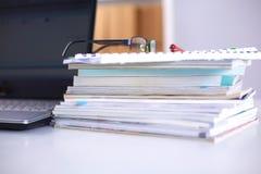 Un carnet, ordinateur portable, stylo, document sur papier de graphique sur la table de bureau derrière les abat-jour blancs Images stock